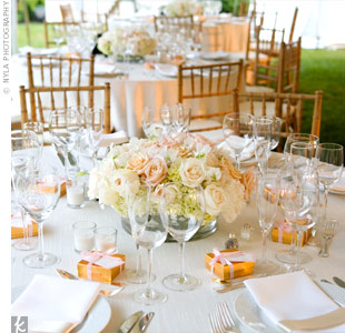 Round glass vases were filled with hydrangeas, roses, peonies, ranunculus and French sweet peas in shades of pink, peach, taupe and ivory. The vases were surrounded by votive candles.