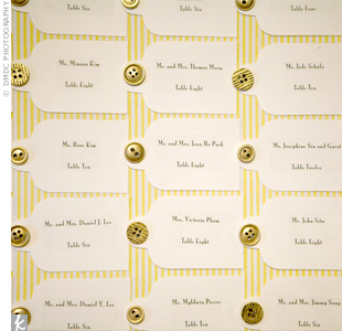 Table numbers were written on hang tags and pinned with gold button thumbtacks to a vintage-framed corkboard covered in yellow and white striped fabric.