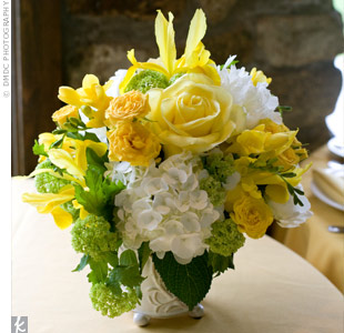 Round white ceramic vases painted with a floral pattern in light gold were filled with ranunculus and hydrangeas in cream, white and yellow, mixed with seasonal greens.