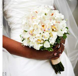 The plum-colored blooms in Heather's bouquet popped against a background of all white roses, stephanotis and cymbidiums. Purple jewels were also added to give the arrangement some extra sparkle.