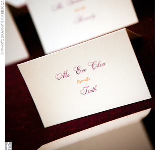 The cream-colored, tented escort cards were printed in the wedding's signature colors: gold and plum.