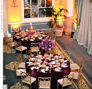 Reception tables were covered with linens and napkins in different shades of deep purple. Orchid blooms were placed on each napkin.