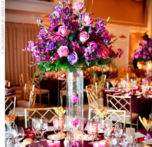 One centerpiece was made of a tall cylinder vase with clusters of purple blooms and hanging crystals. The second centerpiece had three cylinder vases of varying heights holding floating candles, flowers and crystals.