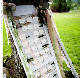 The escort cards were placed on antique white shutters decorated with moss and trailing ribbons. The shutters leaned against one of the large trees outside the reception tent. Each table card had a sepia photograph of a location in South Africa that is special to the bride and groom.