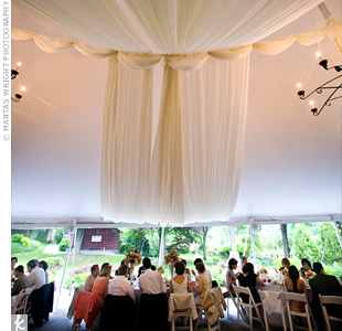 The reception was held under a tent draped in yards of billowy ivory fabric.