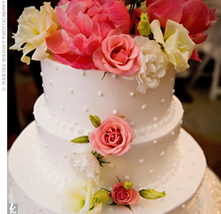 The three-tiered chocolate cake with buttercream icing was decorated with Swiss dots, coral peonies, peach roses, ivory lisianthus and white roses.
