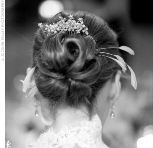 Caroline wore her hair up with a long veil and a sparkly comb for the ceremony. When she took the veil off, she stuck some white striped feathers in her pretty up-do.