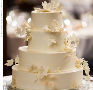 An understated, but elegant confection of buttermilk spice cake and cream cheese filling tempted guests. White foliage draped across all four tiers, matching perfectly with the light buttercream icing.