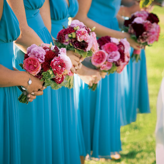 The bridesmaids wore teal V-neck dresses and carried pretty pink and red bouquets.