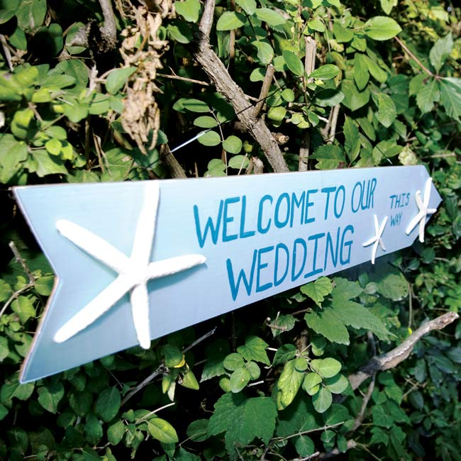 The couple showcased their starfish motif and an aqua and teal color scheme with a handmade sign directing guests to the reception location.