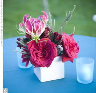 Cocktail tables were set with aqua linens and small, square vases filled with bright pink and red flowers.
