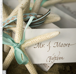The escort cards were actually small, dried starfish tied with calligraphed white tags. The starfish were placed into a large box filled with beach sand surrounded by lush white floral arrangements.