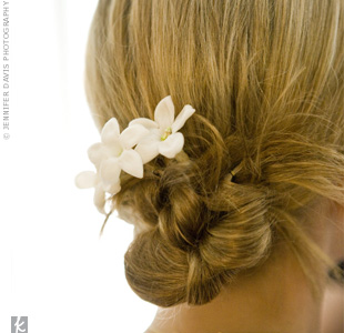 Linda had her stylist pull her hair back into a slightly off-center bun with a few loose pieces in front. She topped it off with a delicate stephanotis.