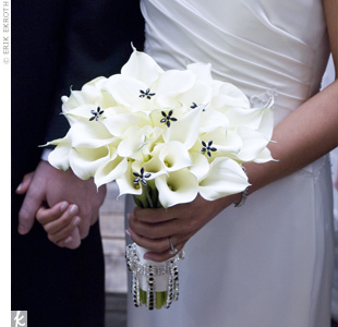 Kim carried a cluster of white calla lilies accented with black floral pins. The stems were wrapped tightly together with white satin ribbon and decorated with a ring of black-and-white crystals hanging around the base.