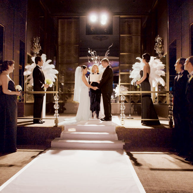 An aisle runner defined the ceremony space, and three arrangements of white feathers were set up on white columns near the altar.