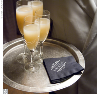 During the cocktail hour, waiters passed Bellinis to guests as a DJ played New York standards to set the mood. Black cocktail napkins, imprinted with the couple's logo, added to the theme as well.