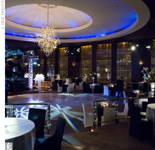 The Rainbow Room was set up with round tables covered with white satin tablecloths and chairs with fitted black-and-white covers. Pinspot lighting highlighted the large feather centerpieces, the cake table, and the dance floor.