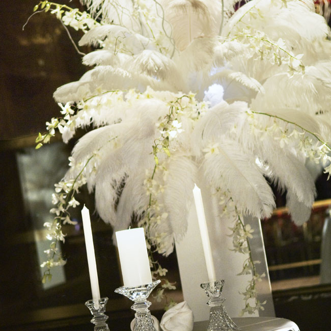 A small round table, set up in the middle of the ceremony space, held the couple's unity candle and was decorated with a tall glass vase filled with white feathers.