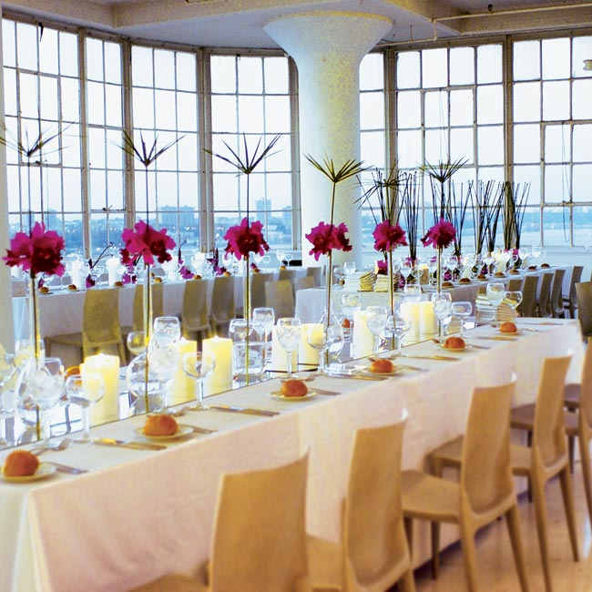 Tall green shoots and bright pink orchids made for modern centerpieces at the long white reception tables. In lieu of the typical chiavari chair, the couple ordered sleek Bellini chairs to coordinate with the modern décor.