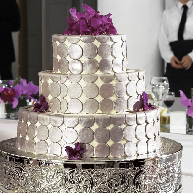 Jacalyn and Rio's red velvet wedding cake with cream cheese frosting was a three-tier confection covered with large silver polka dots and accented with bright pink orchids.