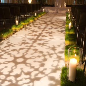 In lieu of a fabric runner, a gothic gobo pattern lit the bride's path to the altar. The aisle was flanked by wheatgrass and candles in glass hurricanes for a sleek, surprising look.