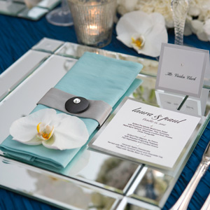 The clean lines of a loft space inspired these geometric place settings, complete with mirrored chargers, square menus and place cards, and a crystal-encrusted button decorating the rectangular folded napkins. A fresh, graphic phalaenopsis orchid was the perfect finishing touch.