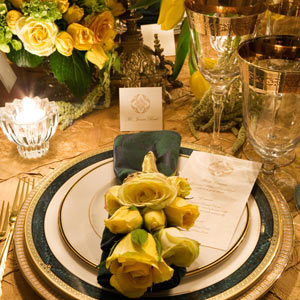 Playful yellow roses looked luxurious when they were paired with these gold-rimmed plates, gold-printed menu cards, and shimmery, jewel-toned linens.  Photo: David Nicholas, New York, DNicholas.com
