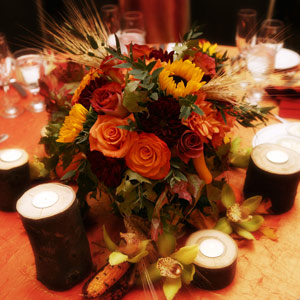 In addition to sunflowers, cymbidium orchids, dahlias, and roses in autumn colors, Shawn spruced up the centerpieces using fall elements like reed, corn, and faux tree stumps.
