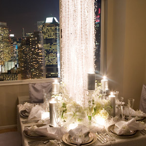 To match the twinkling lights of the New York skyline in the background, Shawn made a cascade of crystals the focal point of this table. Snowflakes on the walls and satiny chair covers added to the sparkle.