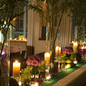 For a sultry, tropical-paradise-at-night feel, Shawn interspersed tall bamboo plants with low arrangements of pink orchids and roses on a long banquet table. Pillar and votive candles provided plenty of light along the table runner.