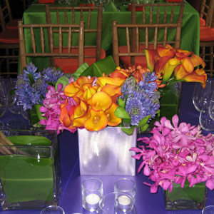 This rainbow bride wanted punches of color at every table for her casual wedding in Upstate New York. A collection of square vases containing green lotus pods, magenta orchids, mango calla lilies, and purple hyacinths warmly welcomed guests as they took their seats.
