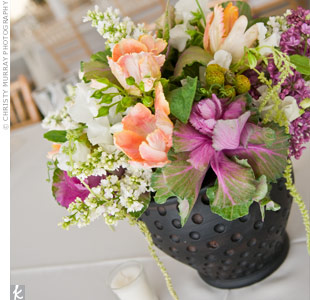 Black vases overflowed with purple and white lilacs, flowering kale, sweet pea vine, apricot parrot tulips, green brunia, hanging amaranthus, peach spray roses and brown galax leaves.