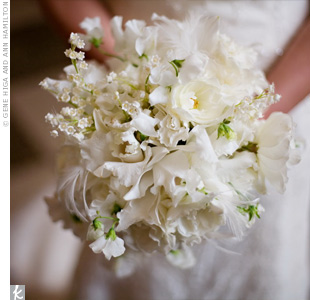 White feathers mixed with Cattleya orchids, sweet peas, and lily of the valley created a soft, airy bouquet.