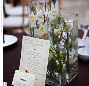 Tall vases filled with white orchids submerged in water created a unique centerpiece while the table card and menu rested against a gold easel.