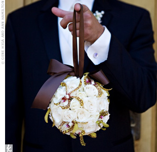 A groomsman in a black Calvin Klein tux showed off the cream spray rose and orchid pomander, which the two flower girls carried down the aisle.