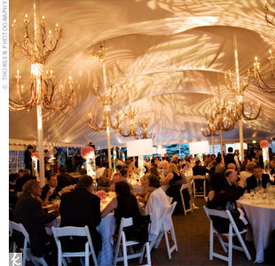 The seated dinner took place beneath a towering tent overlooking the Chicago skyline. Inside, customized lighting with leaf patterns in pink and green tones covered the ceiling and walls. White linens, pink centerpieces and candelabras completed the look.