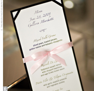 Black-and-white menu cards tied with pink satin ribbon sat at the center of each table.