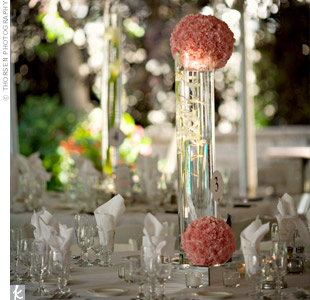 Glass cylinder vases filled with water and orchids had lush pink pomanders on top.