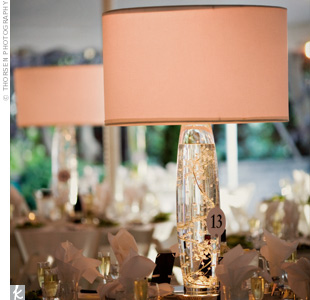 White lampshades topped glass vases filled with water and strands of crystals. Pink light bulbs lit the shades creating a pink-hued glow throughout the space. The display sat on mirrored light boxes.