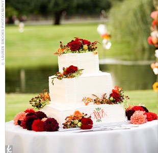 The three-tiered, triangle-shaped wedding cake was frosted with white buttercream dots. The couple's monogram and fresh flowers finished the look.
