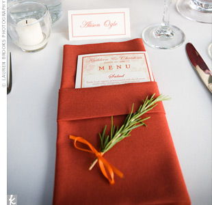 Each place setting had a terra cotta napkin at its center, folded pocket-style to hold the menu cards. A sprig of rosemary tied with orange ribbon was placed at the base of the napkin.