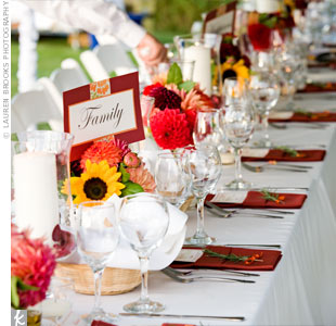 The tables were covered with ivory linens and topped with three small arrangements of dahlias in red, burgundy, orange, and gold. Hurricane lamps with ivory pillar candles surrounded by red rose petals sat in the very middle of the tables.