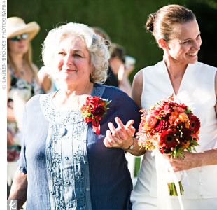 Christina and Kathleen carried vibrant bouquets of dahlias, roses, ranunculus, mango calla lilies, gerbera daisies, and hypericum berries.