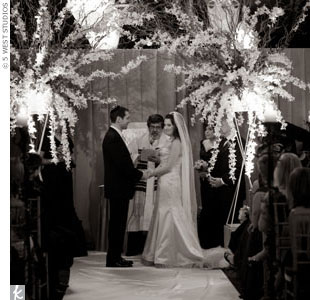 Instead of a traditional huppah, the couple played up their contemporary style with towering arrangements of white orchids that formed a canopy.