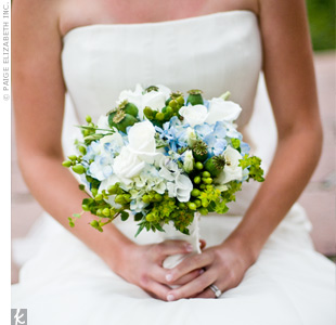 Betsy's favorite color is light blue, so the couple decided to make it one of the main colors at their wedding. Her bouquet featured white roses and light blue hydrangeas accented with green poppy pods and green hypericum berries.