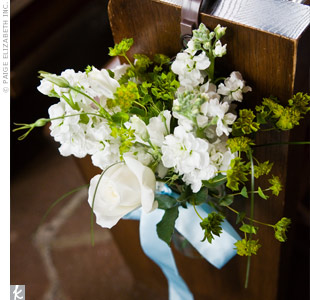 The aisle was adorned with arrangements of white stock and white roses tied with a light blue ribbon.