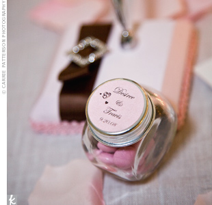 The photo display, ceremony programs, and favors were all DIY projects. To make their edible favors, Desiree filled mini jars with pink and brown M&M's. Each one was personalized with a coordinating tag attached to the jar tops.