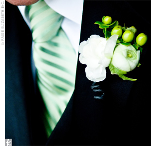 To match his bride's bouquet, Michael wore a white ranunculus with bear grass on his lapel. The groomsmen's boutonnieres were similar, but also contained a few stems of hypericum berries.