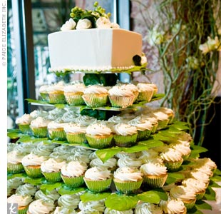 """Cake never tastes as good as cupcakes,"" says Kelly, so the couple opted for a tower of little treats instead of the traditional dessert. Michael didn't want to miss out on the cake cutting tradition, so they topped the tiers with a small cake covered in ranunculus and hypericum berries."