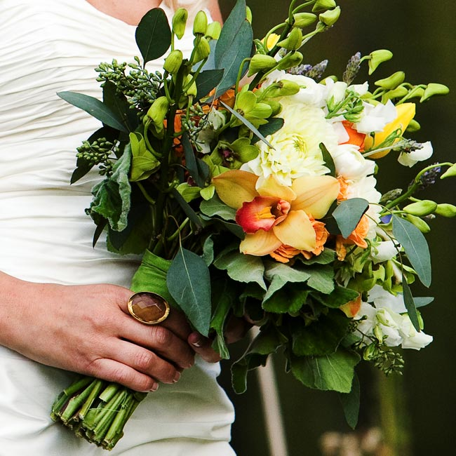 A kaleidoscope of wildflowers and herbs made up the bouquets. The bridesmaids carried a smaller version of Amber's hand-tied arrangement of green dendrobium orchids, orange dahlias and ranunculus, yellow tulips and lavender.